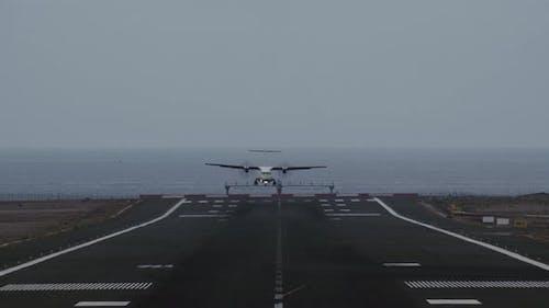 Airplane Coming in for Landing on Runway Overlooking Ocean