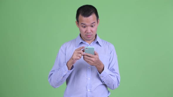 Thumbnail for Happy Asian Businessman Using Phone