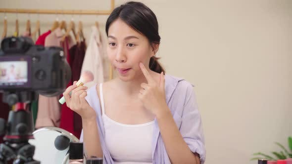 Beauty blogger present beauty cosmetics sitting in front camera for recording video.