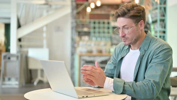 Pensive Middle Aged Man Thinking and Working on Laptop in Cafe