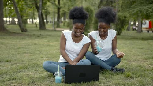 African American Students Sitting in Park with Laptop