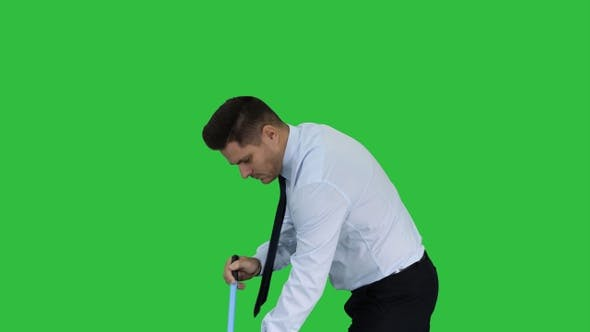 Man in official clother sweeping the floor on a Green Screen