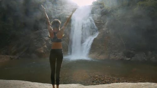 Woman Stands in Yoga Position Against Waterfall