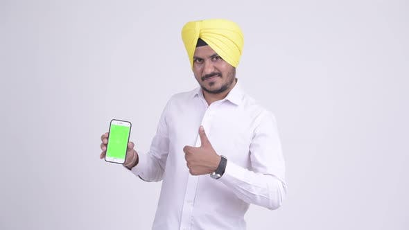 Cover Image for Happy Indian Sikh Businessman Showing Phone and Giving Thumbs Up