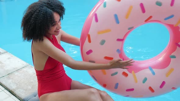 Playful Cheerful Laughing African American Girl Plays with Inflatable Ring, Throws Rubber Pink Donut