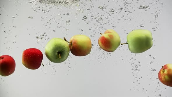 Thumbnail for Colorful Apples Fall Into Water with Splashes and Drops on Clean White Background