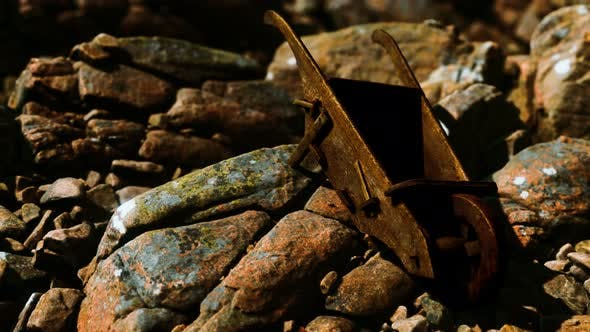 Abandoned Wooden Mine Wheelbarrow on Rocks