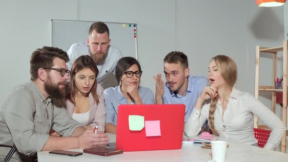 Team Brainstorming in Front of a Laptop