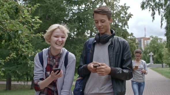 Thumbnail for Teen Couple Using Smartphones while Walking Outdoors