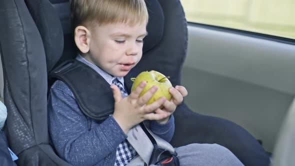 Thumbnail for Kid Eating Apple in Car Seat