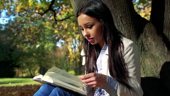 Thumbnail for Slowmotion Young Beautiful Happy Woman Sits in Park and Reads a Book