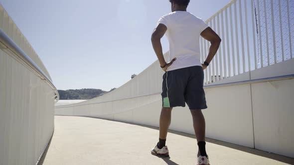 Thumbnail for Rear View of Sporty African American Man Running on Bridge
