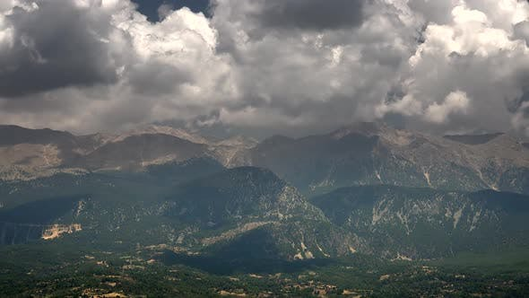 Thumbnail for Forested and treeless high mountain mass under dark clouds