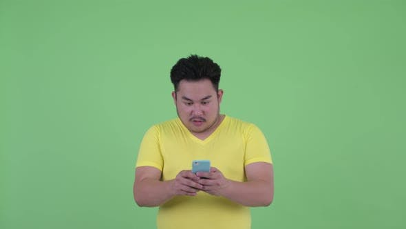 Thumbnail for Face of Happy Young Overweight Asian Man Using Phone and Looking Surprised