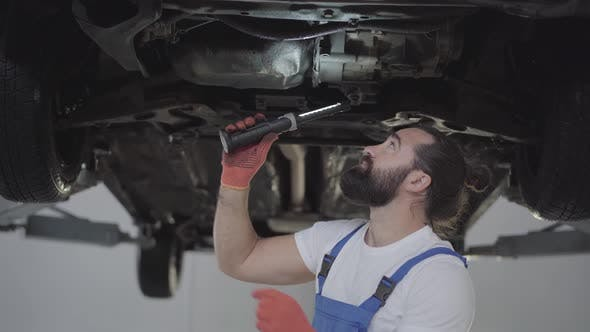 Thumbnail for Successful Bearded Mechanic Inspecting Suspension or Brakes in Car