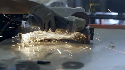 Worker cutting a part of oven in workshop