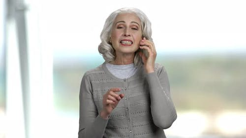 Emotional Woman Talking on Glass Phone.