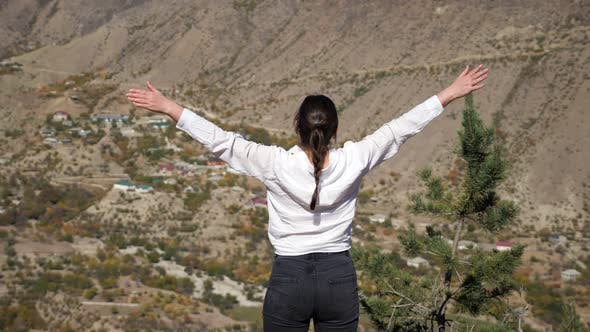 Young Woman in White Shirt Enjoying the View of the Valley with Her Arms Spread Rear View