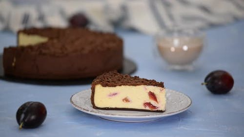 Piece of delicious homemade cheesecake with plums and chocolate crumble.