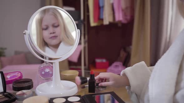 Thumbnail for Reflection in Mirror of Little Cute Caucasian Blond Girl Taking Makeup Brush for Applying Eye