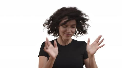 Attractive Carefree Woman with Short Curly Hair Wearing Casual Black Tshirt Dancing and Shaking Head