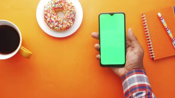 Top View of Man Hand Using Smart Phone on Orange Background