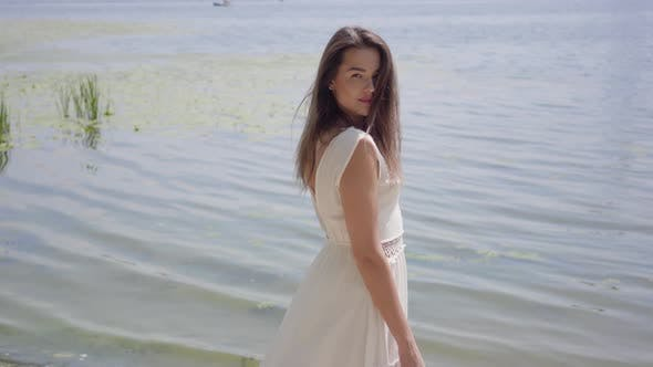 Thumbnail for Portrait Charming Young Girl with Long Brunette Hair Wearing a Long White Summer Fashion Dress