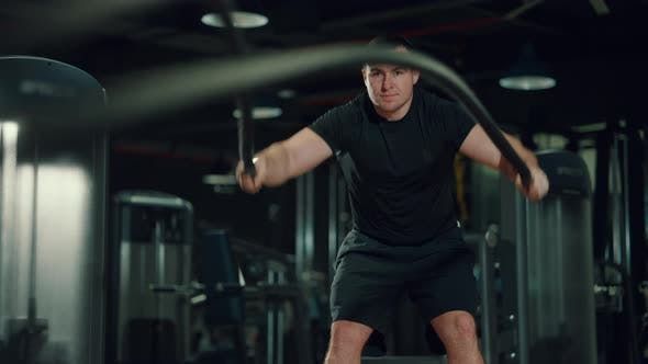Man Exercising with Battle Ropes in Gym