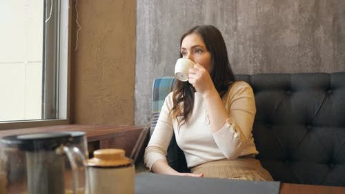 Young Beauty Romantic Woman Drinking Hot Tea or Coffee at Cafe