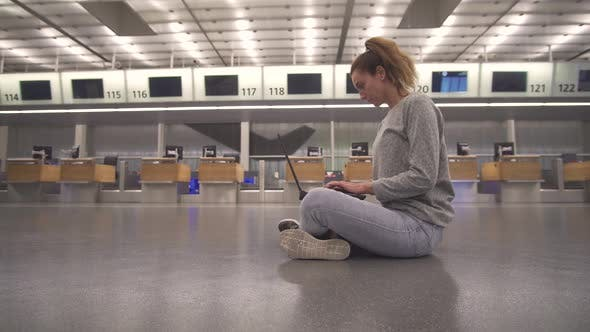 Thumbnail for Girl Sits in the Terminal on the Floor of the Airport Works with a Laptop