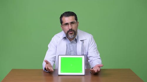 Handsome Persian Bearded Man Doctor Talking While Showing Digital Tablet
