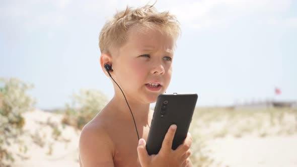 Cute Boy benutzt Smartphone am Strand