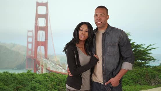 Thumbnail for Black couple looking at Golden Gate Bridge together on vacation in San Francisco, California