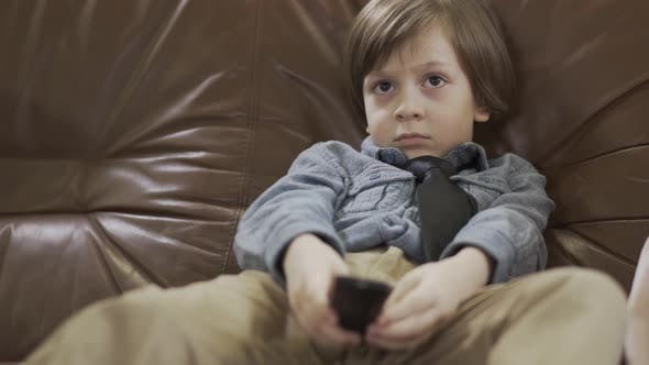Cover Image for The Little Cute Boy Sitting on the Leather Sofa with Legs Apart Changing Channels on TV Using Remote