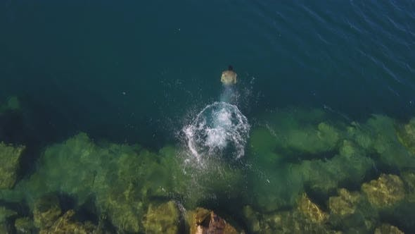 Aerial drone muscular man jumps off a rock into clear blue water In the lake and swim. Top view