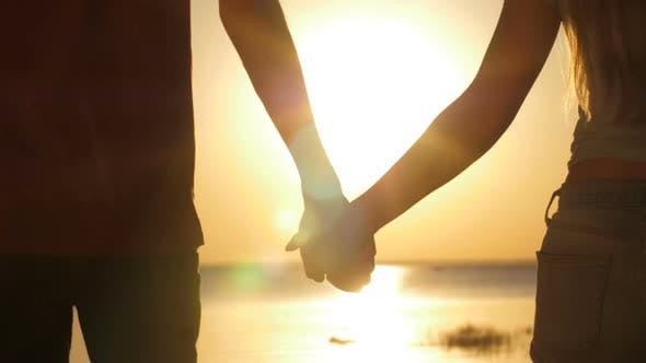 Thumbnail for Couple Holding Hands Walking at Seaside at Sunset