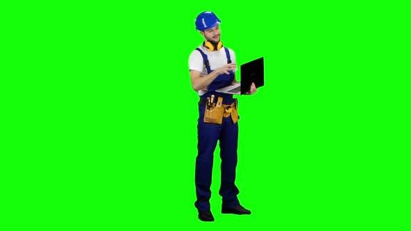 Thumbnail for Ingenieur mit einem Laptop sagt, wie man ein Gebäude baut. Grüner Bildschirm