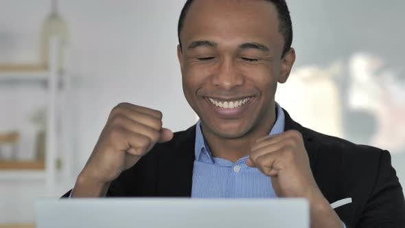 Thumbnail for Close Up of Casual Afro-American Businessman Celebrating Success, Working on Laptop