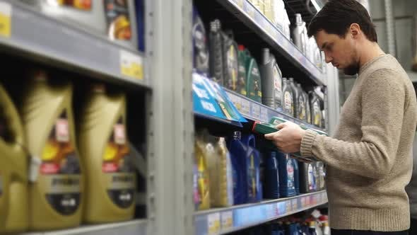 The Young Man Chooses Oil for Machines in the Hypermarket