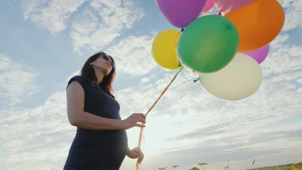 Thumbnail for Carefree Pregnant Woman Playing with Balloons in a Meadow, Against a Blue Sky Background