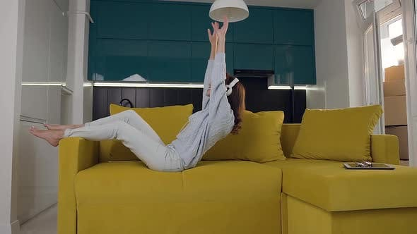 Thumbnail for Happy Cheerful Woman with Headphones Which Falls on the Sofa and Listening Music