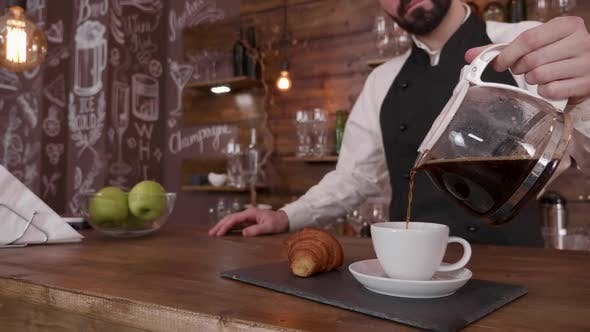 Gently Poring a Cup of Fresh Brewed Coffee on a Tray with a Croissant