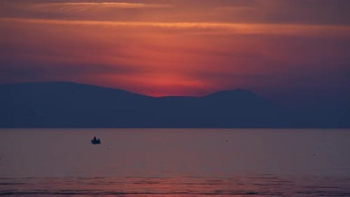 People Silhouettes On Fishing Boat In The Sea At Sunset