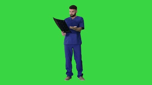 What Is That? Male Doctor Examines X-ray Picture of a Human Brain on a Green Screen, Chroma Key.