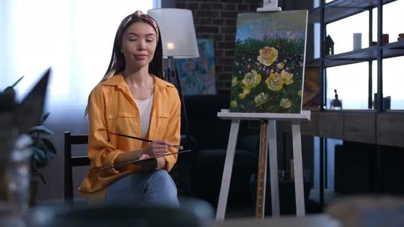 Thumbnail for Attractive Asian Female Artist Sitting Near Canvas