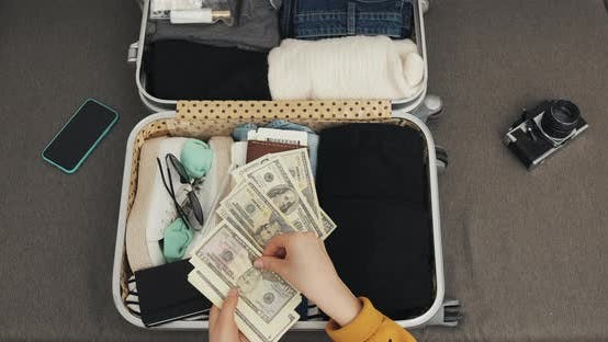 Thumbnail for Money for Travel. Woman Hands Counting Dollar Bills on the Suitcase Background