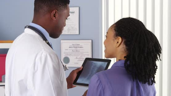 Thumbnail for African American woman with neck pain talking to doctor about x ray on tablet