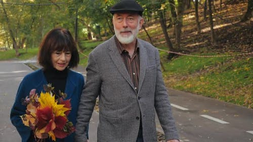 Close-up View of Lovely Smiling Senior Citizens of Wife with Bouquet of Leaves and Husband Dressed