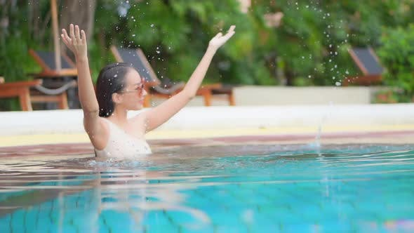 Young asian woman enjoy around outdoor swimming pool for leisure