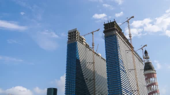 Construction of a Modern Skyscrapers Using Tower Cranes. Timelapse. Moving Clouds on Blue Sky